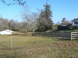 Road Frontage on a beautiful fenced 5 acres, small outbuilding, carport, and tractor behind house go with house and are NOT FOR SALE SEPARATELY.  Huge Potential for rental property available.  Water source on property and barn for livestock.