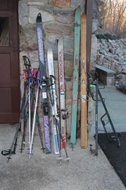 ski rack, skis and poles galore - some w/ vintage cable binding