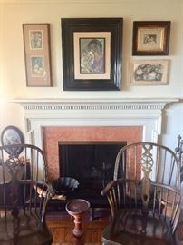 Group of paintings by Simone over a classic fireside hearth