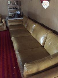 Extra long leather sofa has a companion three-cushioned sofa