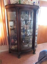 Oak curved glass china cabinet with carved paw feet.