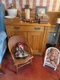 Pine wash stand with oil lamps, wood boxes, and framed early photo. The child's chair has a raggedy ann doll and the doll chair has a bear sitting in it.