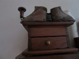 Early coffee mill with early child shoes.