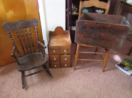 Pressed back oak child's rocking chair on the left. Spice wall cabinet, center, and pine box on the right.