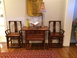 area rug, lamp , wooden chairs and table with drawer