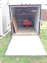 Rear open view of the Cargo Craft Trailer. Size 6' wide x 12' long x 6' high. This trailer features AC Electricity, DC  Interior Lights, overhead ventilation, built in storage binds, wall storage, and exterior side exit door. A Great Value! Must see!!!