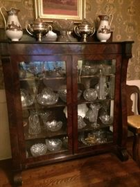 Empire mahogany and glass china cabinet full of beautiful cut glass                                                                        On top-pair of silver tureens-Medallion pattern, Pair of Etruscan vases, cut glass eggnog bowl
