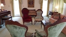 Broad view of living room showing mahogany chairs, 2 sofas, piano and more - very lovely.