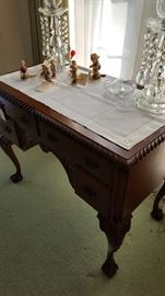 Mahogany writing desk with lamps and Hummel figurines.