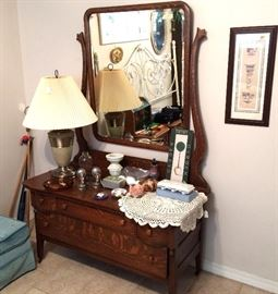 Antique oak lowboy dresser with tilt mirror. Brass accent table lamp with shade. Ottoman. Wall sconces with mosaic detail. Vintage lace doily. Vintage Avon soaps. Wall art. Scrolled cast metal headboard in white. Haeger pottery pedestal candle holder. Walking canes.