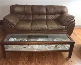 Custom-made shadow-box coffee table, shown as showcase of shells from beaches in Mexico and South America; faux leather sofa