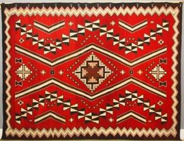 "An 11.1 x 8.4' circa 1930 Navajo Ganado regional rug.  Woven of handspun wool, in natural white, black, gray, dark brown and light brown on a red ground, with three serrated diamonds along the center flanked by angular bars and serrated devices, within a serrated border.  Light wear; several stains.  133 x 100"".  ESTIMATE $6,000-8,000  Provenance:  Commissioned by John C. Holley, Jr. of Grosse Pointe, Michigan from the Hubbel Trading Post, circa 1930, for use in his hunting lodge near Lake Placid, New York.  Christopher Selser of Park Avenue, New York, the former Director of ACA American Indian Arts who, along with Alice Kaufman, authored ""Navajo Weaving Tradition: 1650 to the Present"".  Purchased by Robert Teeter, June 1983.  The original correspondence between Teeter, Kaufman and Selser, pertaining to this item, is available for review."