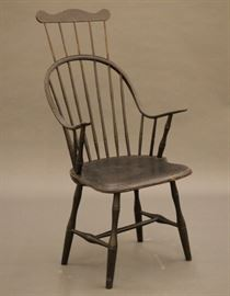 "A late 18th/early 19th century New England continuous arm, comb back Windsor armchair.  Seven spindle back, shaped hand holds, turned spindles, shaped plank seat and turned stretcher base.  Hickory and Maple construction with a Pine seat.  Older Black paint with some wear, crack in seat, feet ended out approx. 5"".  20 1/2 x 17 1/2 x 44 3/4"" high overall.  ESTIMATE $400-600"