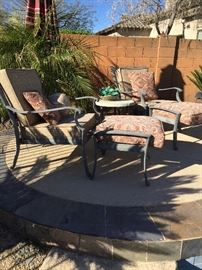 Wrought iron lounge chairs and custom Sunbrella cushions with side flagstone & wrought iron table