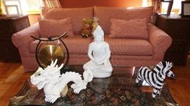 Sofa Sleeper with unique decor items: Buddha, zebras, Dragons. Glass and brass antique coffee table, 2 wicker end tables with file drawers. Traditional style area rug