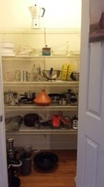 pantry stocked with pots, pans, serving tools, bakeware, blender, juicer, etc.