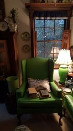 green winged back chair, books, lamp, and decorative plates