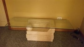 Stone base, glass top coffee table.