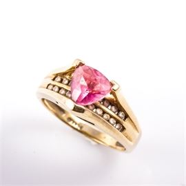 14K Yellow Gold, Tourmaline, and Diamond Ring: A 14K yellow gold ring featuring one center trillion cut pink tourmaline mounted in a high v-prong setting atop two rows of channel set round brilliant cut diamonds.