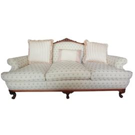 Vintage Sofa: A vintage sofa. Features an exposed wood frame with carved detail to the top rail and front leg supports. It is upholstered with a floral patterned fabric and has braided gimp trim. Matches item 17LAX062-002.