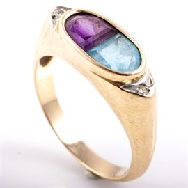 14K Yellow Gold, Amethyst, Blue Topaz, and Diamond Ring: A 14K yellow gold ring featuring faceted half moon shaped amethyst and blue topaz stones mounted in an oval bezel setting, flanked by diamond side stones.