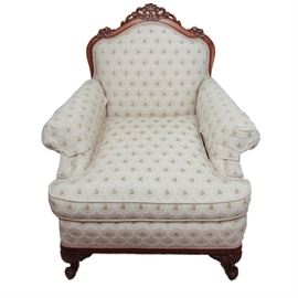 Vintage Armchair: A vintage armchair. Features an exposed wood frame with carved detail to the top rail and front supports. It is upholstered with a floral patterned fabric and has braided gimp trim. Matches item 17LAX062-013.