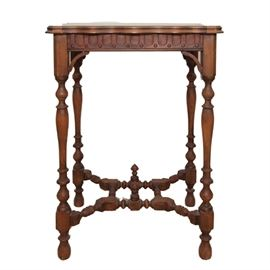 Antique Victorian Carved Side Table: An antique victorian side table. This table features a wooden construction with an inlay design to the top and scalloped edges. It rests on turned supports with a carved stretcher.