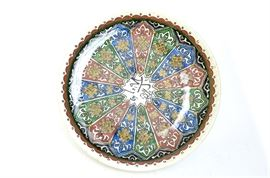 Early 20th Century Arabic Plate: An early 20th century Arabic plate. This plate features red, blue, and green underglaze painted patterns with Arabic writing at center. The underside is impressed with a stamp.