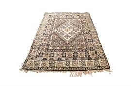 Hand Knotted Rug from Tunisia (ca. 1950): A hand knotted rug from Tunisia ca. 1950. The rug has a center diamond surrounded by various geometric shapes. Woven in a gray and beige color palette the rug has a white knotted fringe at each end.