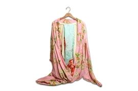 Japanese Silk Kimono from the 1950s: A vintage Japanese silk kimono from the 1950's. The silk dress has a printed floral and lantern design on a pink background. The kimono has a large sleeve and spode with red lining. A blue silk obi with red embodied circles accompanies the kimono.