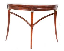 Bombay Company Mahogany Demilune Table: A mahogany demilune table by the Bombay Company. This piece is constructed from solid mahogany, and it features a demilune top over a carved apron and three tapered legs with brass accents at the top and curved stretchers.