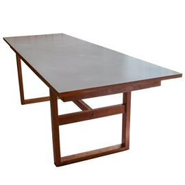 Mid-Century Modern Dining Table by Otmar: A mid-century modern dining table crafted by Otmar. The table has an affixed white laminate top with a trestle base and center stretcher.