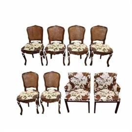 Wooden Floral Motif Chairs: A set of chairs. This selection includes eight pieces, two of which are armchairs and six without arms.The chairs feature foliate upholstery in shades of brown, green, and white.