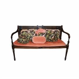 Wooden Bench with Cane Seat: A wooden bench with cane seat. This piece features a wooden frame with a black antiqued finish and painted gold tone and red accents, cane seat, upholstered pink seat cushion, armrests, and turned legs. Also featured is a selection of black and pink accent pillows.