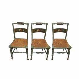 Hand-Painted Accent Chairs: A set of hand-painted accent chairs. This collection of three chairs with wicker seat and green painted wood frame features a turned top rail with floral pattern and a horizontal back splat with matching design rising on front turned legs with turned stretcher. These pieces are unmarked.