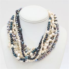 Multi-Strand Pearl Necklace: A multi-strand pearl necklace. This necklace features multiple strands of various colored and white pearls. The back attaches with a large black toggle clasp.