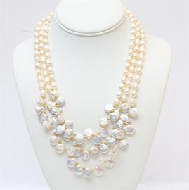 Pearl Opera Necklace: A pearl opera necklace. This necklace features three strands of freshwater pearls and a silver-tone S-hook closure. Between the larger pearls are small gold tone beads.