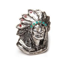 "Sterling Silver Imitation Stone and Diamond Statement Ring: A sterling silver, ruby colored rhinestone, imitation turquoise and diamond statement ring. This ring depicts a Native American elder in traditional feathered headdress decorated with four ruby colored rhinestones and six simulated turquoise pieces. The eyes have two diamonds set in them. Along the front is a marking for ""Denver, Colorado"" and on the interior of the band is a mark for ""925"". The total approximate weight inclusive of non-sterling materials is 1..13 ozt."