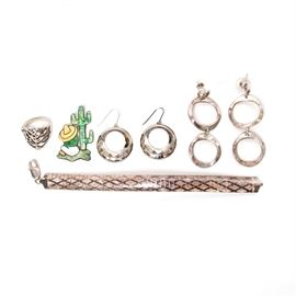 Sterling Silver Jewelry: A mixed lot of sterling silver jewelry. This lot is made up of two pairs of earrings, a pin, a ring, and a bracelet. The bracelet is a round chain with a lattice design and a lobster claw clasp. The first pair of earrings has a fish hook and a single circular dangle. The second pair of earrings has a double circular dangles with bullet clutch earring backs. The pin depicts a person sitting beside a cacti and wearing a hat, green shirt, and white pants. The ring depicts a tree design. All of the items are marked silver. The total weight is approximately 1.51 ozt.