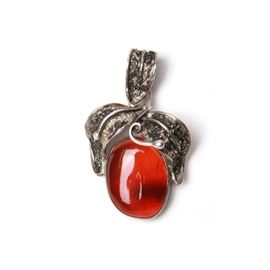 Sterling Silver Copal Pendant: A sterling silver copal pendant. This piece features an orange-red opaque stone to the center adorned with sterling silver foliage to the top. A rounded foliage style sterling hook is to the top. The approximate weight is 0.29 ozt.