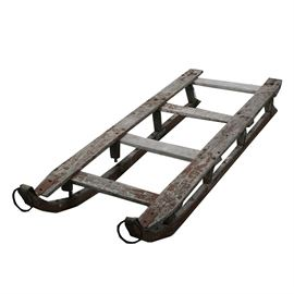 Antique Red Painted Wood and Iron Sled: An antique red painted wood and iron sled. This freight sled features wrought iron wrapped runners with large rings to the front, pegged construction, and an old red paint finish. The piece is unmarked.