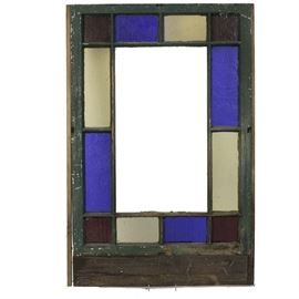 Vintage Stained Glass Window: A vintage stained glass window. This window features alternating stained glass panes, with square red corners and blue and colorless panes in between. One side exhibits an old dark green paint while the other is in white. The piece is unmarked.