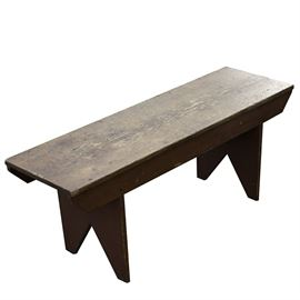 Pine Bench in Old Red Paint: A pine bench in old red paint. This early pine wood bench features a single board top with angle-arched feet and trapezoidal aprons. The latter two features both still exhibit an old red paint finish.