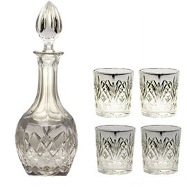 "A Waterford Decanter with Glasses: A Waterford decanter with glasses. The crystal decanter has cut details along the base and an almond shaped stopper seal. Included are four matching Waterford whiskey glasses. Etched on the bottom of the decanter and glasses are ""Marquis by Waterford."""