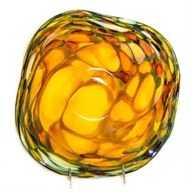 Decorative Blown Glass Bowl: A decorative blown glass bowl. The glass bowl has a waved shaped lip. The bowl is featured in various shades of green and yellow.
