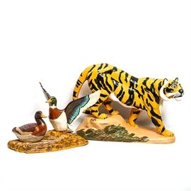 "Pair of Hand Painted Figurines: A pair of hand painted figurines. The Figurines include a single tiger and a pair of ducks. The tiger figurine displays a tiger walking on a a sand colored base with grass painted on the side . The duck figurine displays a pair of ducks with one duck spreading his wings and the other sitting on a base painted in various shades of brown. The tiger figurine is marked ""R.R."" and the duck figurine is marked ""1882""."