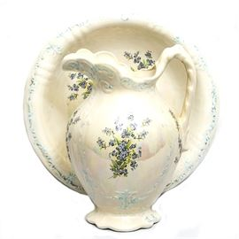Hand Painted Wash Basin and Pitcher: A hand painted wash basin and pitcher. Both pieces match with an iridescent glaze on a cream paint. The pieces feature bouquets of blue flowers. The pitcher has an ornate handle and lip.