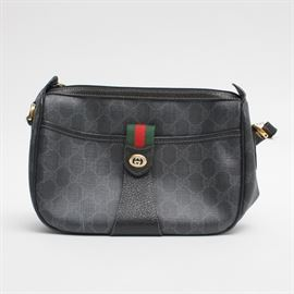 Gucci Vintage Black Monogram Shoulder Bag: A vintage Gucci Accessory Collection bag in black coated canvas with matching leather trim. The body of the bag features the classic Gucci monogram print as well as the green and red striped webbing which acts as a closure for a front slip pocket. The interior offers one zippered wall pocket and is marked with the serial number, 89.02.032. The original dust bag is included.