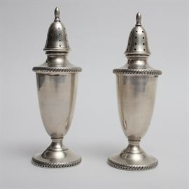 "Hunt Silver Co. Sterling Silver Footed Salt and Pepper Shakers: A pair of sterling silver salt and pepper shakers by Hunt Silver Co. These footed shakers feature tapered bodies with a gadrooned edge at the pedestal base and shoulder, and pierced tops with bullet finials. The pieces feature the maker's mark for Hunt Silver Co., ""sterling"" and the pattern number 400."