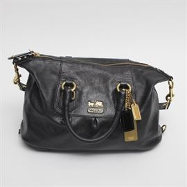 Coach Madison Sabrina Black Leather Handbag: A black leather Coach Madison Sabrina handbag. This bag features double handles and a shoulder strap, with brass tone hardware. The purple-line interior has a wall zip pocket and wall slip pockets. Serial number F0871-12937.